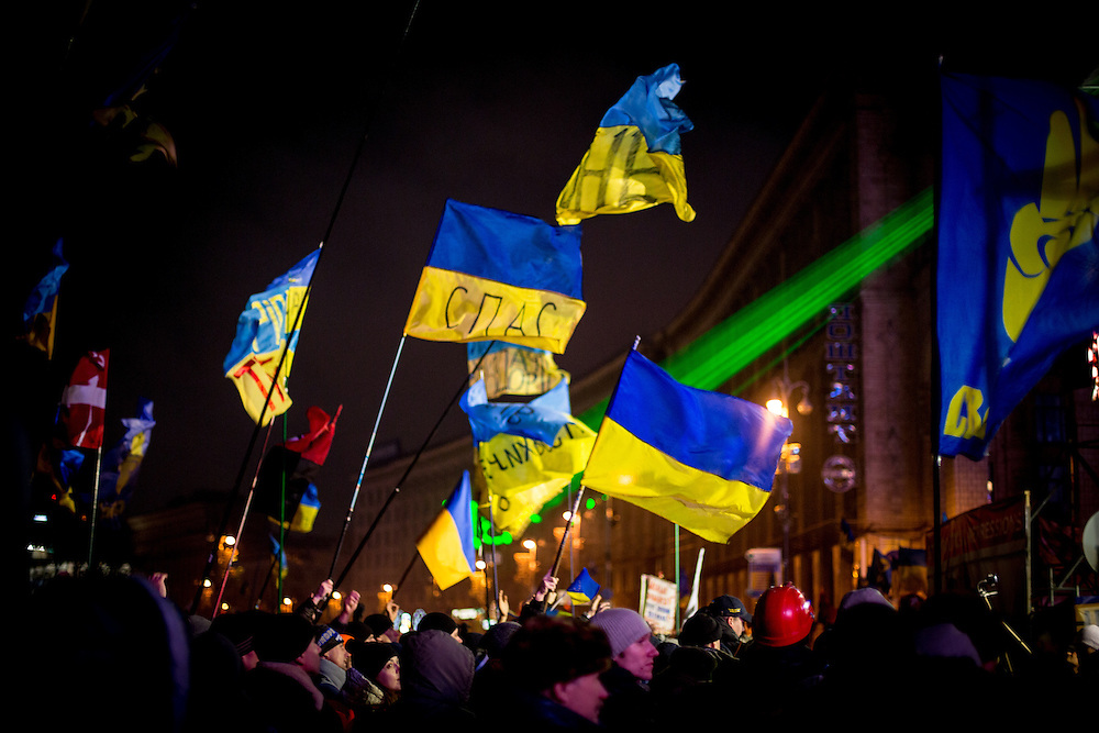 People wave Ukrainian flags in front of the stage, on the Independance Square, at night.