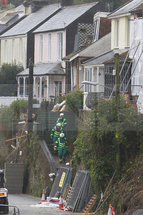 © Licensed to London News Pictures. 22/03/2013. Looe, UK. Paramedics leave the remains of a house that collapsed after heavy rain caused a land slide on Sandplace Road, Looe this morning. A body has been found this afternoon, It has yet to be identified but is presumed to be that of the homeowner. Photo credit: Ashley Hugo/LNP