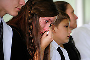 { WILSON MEMORIAL } Hannah Johnson wipes away tears with her family at a memorial service for her sister, Sarah, who was killed in an explosion in Wilson, Saturday, Aug. 4, 2012. {Photo by Nick Agro / Buffalo News}