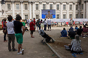 Spectators watch live TV coverage of the Diving event at the old Royal Naval College, Greenwich on day 4 of the London 2012 Olympic Games. Greenwich Park is hosting the Olympic Equestrian competitions, plus the combined running and shooting event of the Modern Pentathlon. The Old Royal Naval College is the architectural centrepiece of Maritime Greenwich, a World Heritage Site in Greenwich, London. The buildings were originally constructed to serve as the Royal Hospital for Seamen at Greenwich, now generally known as Greenwich Hospital, which was designed by Christopher Wren, and built between 1696 and 1712.