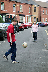 Boy playing football in the street with his father,