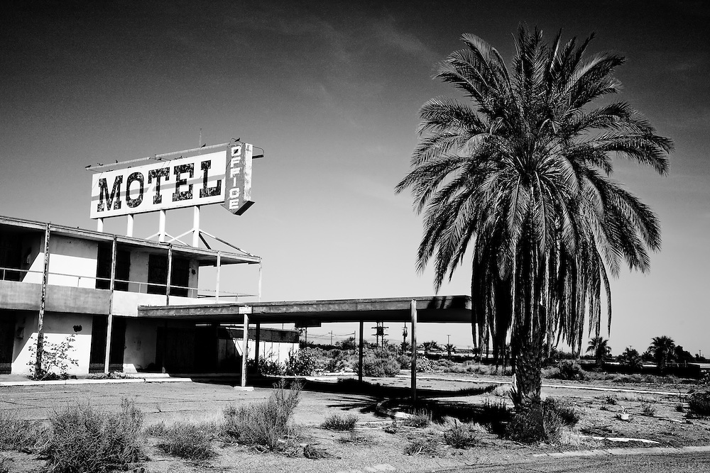 An abandoned North Shore motel along the shores of the Salton Sea. Lone palm tree visible in the foreground.