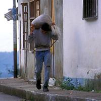 Hombre caminando por la acera de la calle con saco a espaldas, Altamira de Caceres, Estado Barinas, Venezuela.
