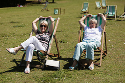 © Licensed to London News Pictures. 22/07/2014. London, UK. Two women relaxing in deckchairs and enjoying the sunshine in St Regents Park in central London this lunchtime. Photo credit : Vickie Flores/LNP