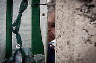 Palazzo San Gervasio (PZ) 14.06.2011 - Centro di Identificazione ed Espulsione. Una delegazione di parlamentari composta dai deputati Jean Leonard Touadi (Pd), Rosa Villecco Calipari (Pd) e Giuseppe Giulietti (Gruppo misto) - che oggi e' entrata nel Centro di identificazione ed espulsione (Cie) di Palazzo San Gervasio - ne ha chiesto ''l'immediata chiusura, per via delle inaccettabili condizioni di detenzione in cui versano 57 giovani tunisini''. Nella Foto: Un poliziotto al cancello..Foto Giovanni Marino