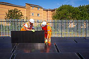 A train travels past an array of solar panels as workmen install the last panel next to the line near Aldershot Railway Station.  This innovative project is the first in the UK to power the railway with electricity generated from solar power and, if successful, could see many Network Rail sites across the country adapting this sustainable energy approach. Riding Sunbeams is a social enterprise, run by 10:10 Climate Action. Built with Community Energy South and partnered with Network Rail and The Department for Transport and by InnovateUK.  Aldershot, Hampshire, United Kingdom. Riding Sunbeams is a world leading project to connect solar panels directly into electrified rail routes to power the trains. Direct supply of solar power to rail traction systems has never been done. But it has huge potential - from metros, trams and railways in the UK and around the world.<br /> (photo by Andy Aitchison / 1010 Climate Action)