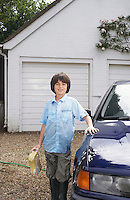Portrait of boy (7-9) posing by washed car