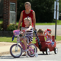 Natalie Willingham, 7, rides her bike as she and her mother Susan pulls her siblings Sarah, 4, and Charlie, 2, in a wagon prior to lining up for the Joyner Neighborhood Parade Wednesday morning in Tupelo.