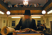 "Rabbi Herschel Gluck of Walford road Synagogue reads the Megillah ""The Scroll of Esther"" during the Jewish festival of Purim. Women and children listen to the Rabbi from a balcony upstairs."