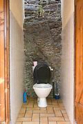 modern toilet built against a rock wall