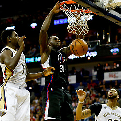 Dec 28, 2016; New Orleans, LA, USA;  Los Angeles Clippers forward Brandon Bass (30) dunks over New Orleans Pelicans guard Jrue Holiday (11) during the second quarter of a game at the Smoothie King Center. Mandatory Credit: Derick E. Hingle-USA TODAY Sports