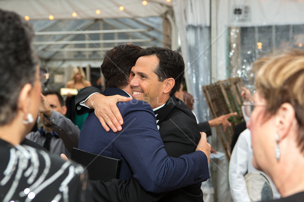 two men hugging at a wedding reception