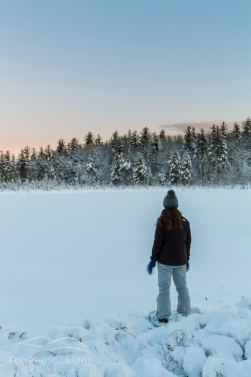 A girl on the edge of Round Pond in winter waiting for the sunrise. Barrington, New Hampshire.
