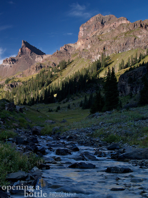 The Middle Fork of the Cimmaron River flows beneath Coxcomb Peak (left, 13,656 feet) and Redcliff (right, 13,642 feet) in the Uncompahgre Wilderness, Colorado.