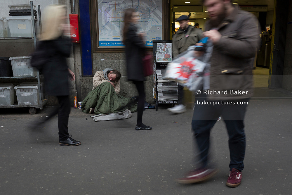 As passers-by blur when walking past, a homeless street beggar sleeps on the ground outside Holborn tube station, on 22nd November 2017, in London England.