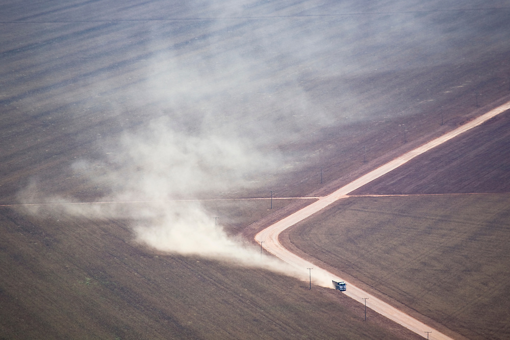 A semi truck leaves a cloud of dust and dirt as it drives throug farmland in the Tangana Da Serra region of Mato Grosso, Brazil, August 9, 2008. Daniel Beltra/Greenpeace