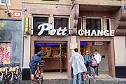 Toeristen staan met hun huurfiets bij het geldwisselkantoor Pott Change aan het Damrak in Amsterdam.<br /> <br /> Tourist with their rental bikes at the money exchange office at the Damrak in Amsterdam.