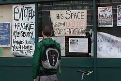 © Licensed to London News Pictures. 19/06/2015. London, UK. A passer by looks at the occupation signs in the window at the Elephant and Castle pub in Southwark, south-east London. A group of activists have occupied the Elephant and Castle pub and are squatting in it to prevent Foxtons Estate Agents from opening an Estate Agent branch. The activists, who are against gentrification want the historic pub site to become a community asset with open use. The Elephant and Castle pub closed earlier this year after its license was revoke and in April, representatives of Foxtons notified planning authorities that they intend to open a branch of the estate agents chain in the pub. Photo credit : Vickie Flores/LNP