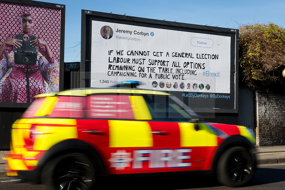 "© Licensed to London News Pictures. 14/02/2019. London, UK.  A fire car drives past a new Jeremy Corbyn billboard from ""Led By Donkeys"" that has been put up in Mr Corbyn's Islington constituency with a message asking for Labour party support on a pubic vote on Brexit. A previous billboard, errected in the same place on Monday was reportedly removed by Islington Council, who later replaced the blank board when challenged. Photo credit: Vickie Flores/LNP"