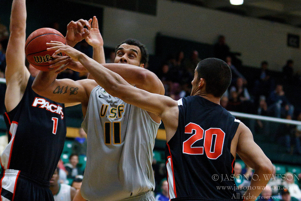 Dec 10, 2011; San Francisco CA, USA;  San Francisco Dons center Justin Raffington (11) is fouled by Pacific Tigers forward Ross Rivera (20) during the first half at War Memorial Gym.  Mandatory Credit: Jason O. Watson-US PRESSWIRE