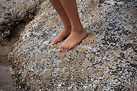 A young girl with pink toenail polish stands On the rocks of tide pools near Lincoln City Oregon.