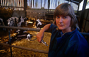 A portrait of a young lady vet, Diana Stapleton with cows at Manor House Farm, Barnoldswick near Settle, North Yorkshire, England. Diana has just delivered twin calves and checks on other members of the herd before leaving for another appointment. Diana Stapleton belonged to the Dalehead Veterinary Group based in nearby Settle for 15 years, covering a 20-mile area of 500 remote farms though she specialised in small animals and farmwork before dying suddenly at the age of 39.