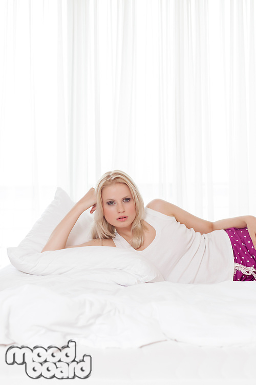 Portrait of blond young woman relaxing in hotel room