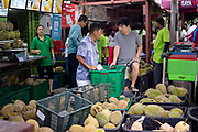 Tan Eow Chong (center left) speaks with his protege son Tan Chee Keat (center right) as they stand in Durian Kaki, Tan Eow Chong's roadside durian stall, in Bayan Lepas, Pulau Pinang, Malaysia on June 17th, 2019. Tan Eow Chong is an award-winning durian farmer famed for his Musang King variety, and last year exported 1000 tons of the fruit to China from his family-run durian empire, expanding from an 80 acre farm to 1000 acres.  Photo by Suzanne Lee/PANOS for Los Angeles Times