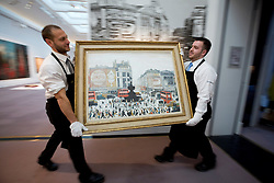 "© Licensed to London News Pictures. 21/03/2014. London, UK. Sotheby's auction house staff move ""Piccadilly Circus London"" (1960) (est. GB£4,000,000-6,000,000) by British artist LS Lowry during the press view for a new sale of the artist's work in London today (21/03/2014). The auction, entitled ""Lowry: The AJ Thompson Collection"", features works by Lowry assembled over a 30 year period by collector A.J. Thompson. Photo credit: Matt Cetti-Roberts/LNP"