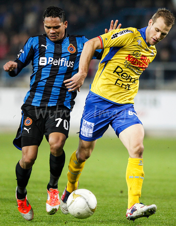 Carlos Bacca of Club Brugge (L) and Siebe Blondelle of Waasland Beveren fight for the ball during the Belgian Jupiler League soccer match between Waasland Beveren and Club Brugge, at the Freethiel stadium in Beveren, Belgium, 17 November 2012.   EPA/Thierry Roge