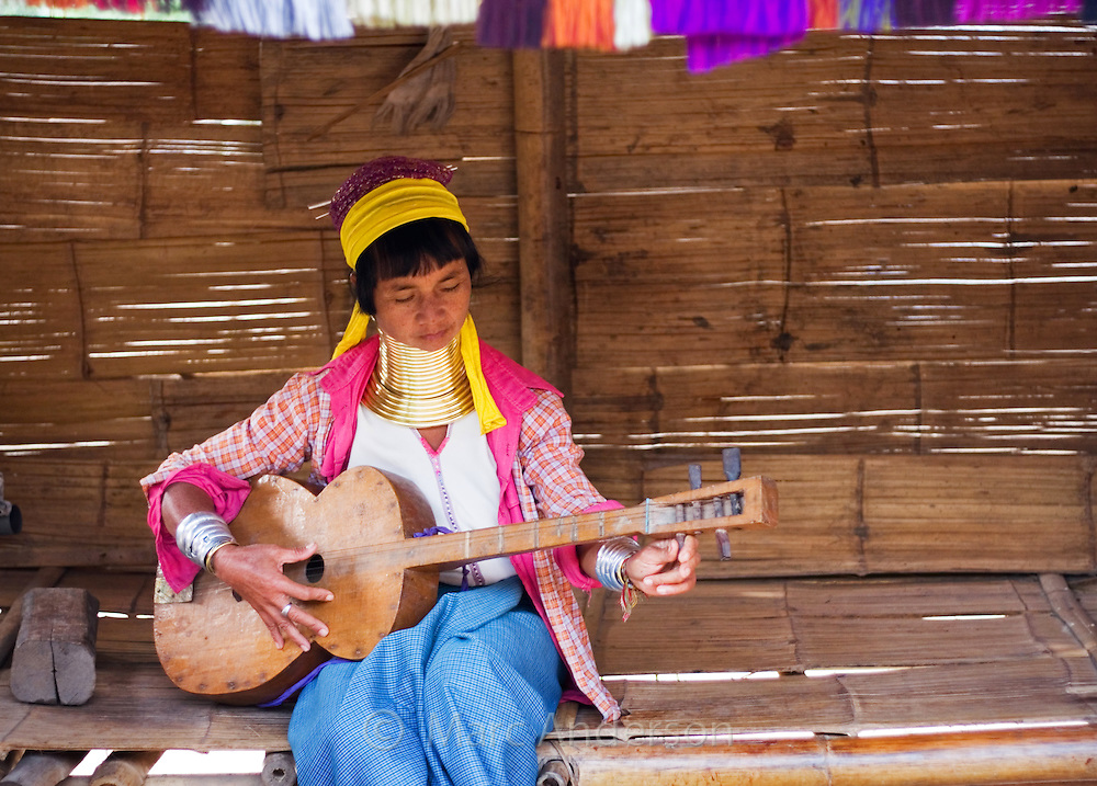 Woman from the Padaung long neck hill tribe playing a guitar near Tha Ton, Chiang Mai Province, Thailand