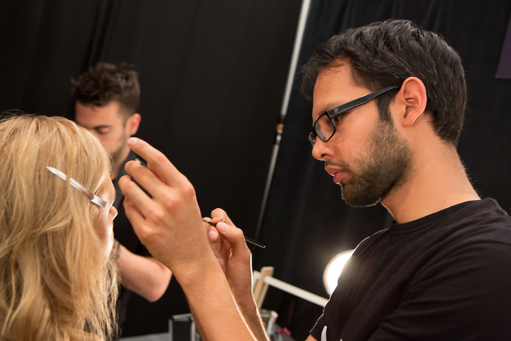 Makeup artist putting the finishing touches on a model.
