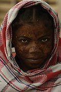 Mahafaly woman (Those-who-make-taboos) wearing sandalwood face paste to protect from the sun and as a beautification. Ampanihy, south-west coast of MADAGASCAR<br />The Mahafaly probably arrived to Madagascar around the 12th centurey from Africa and live in the sw desert areas around Ampanihy and Ejida. They are farmers, with maize, sorgho and sweet potoatoes as their main crops and cattle rearing occupies a secondary place. They kept their independence under their own chiefs until French occupation and still keep the bones of some of their old chiefs - this is the 'Jiny' cult. The villages usually have a sacrificial post, the 'hazo mango' on their east side where sacifices are made. Their large rectangular stone tombs which are decorated with wooden carvings 'aloalo' and the horns of all the zebu slain at the funereal are very eleborate.