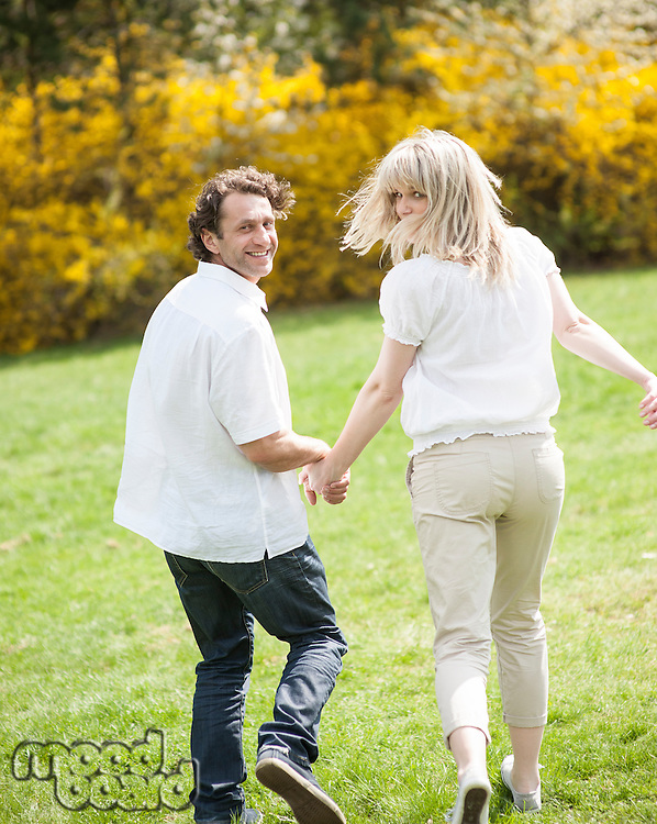 Couple holding hands with back to camera running through park