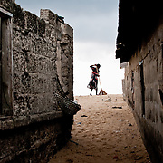 Every morning the women of Totope, a village near Ada in Ghana, sweep the beach and bury the rubbish that has been swept down the coast overnight from the cities of Accra and Tema. As the sea continues to advance on the village it periodically buries homes in sand and garbage. 9 March 2010.