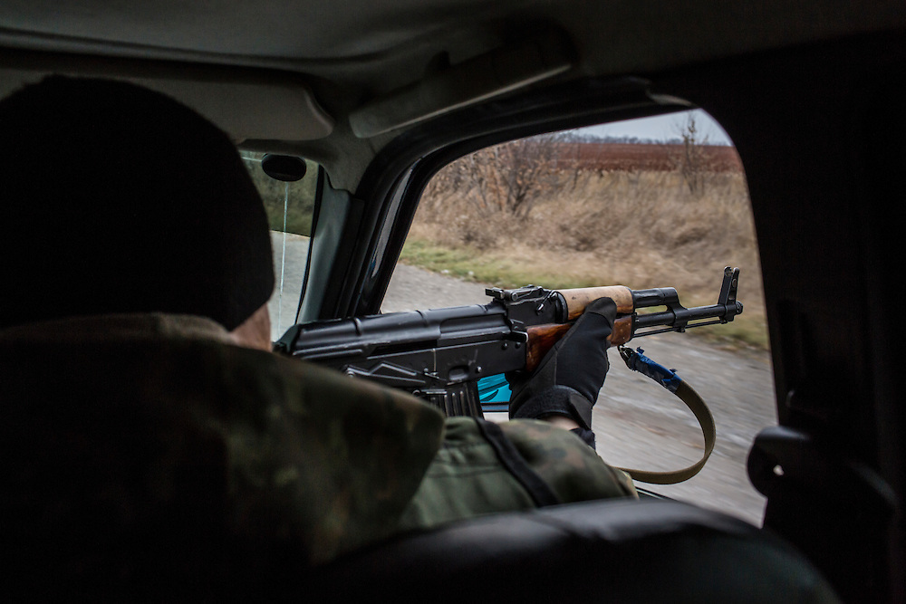 PERVOMAISKE, UKRAINE - NOVEMBER 17, 2014: A member of the Dnipro-1 brigade, a pro-Ukraine militia, aims his gun out the window of his car to counter potential snipers on a highway near Pervomaiske, Ukraine. CREDIT: Brendan Hoffman for The New York Times