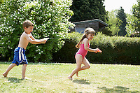 Boy shooting girl with water pistol in back yard