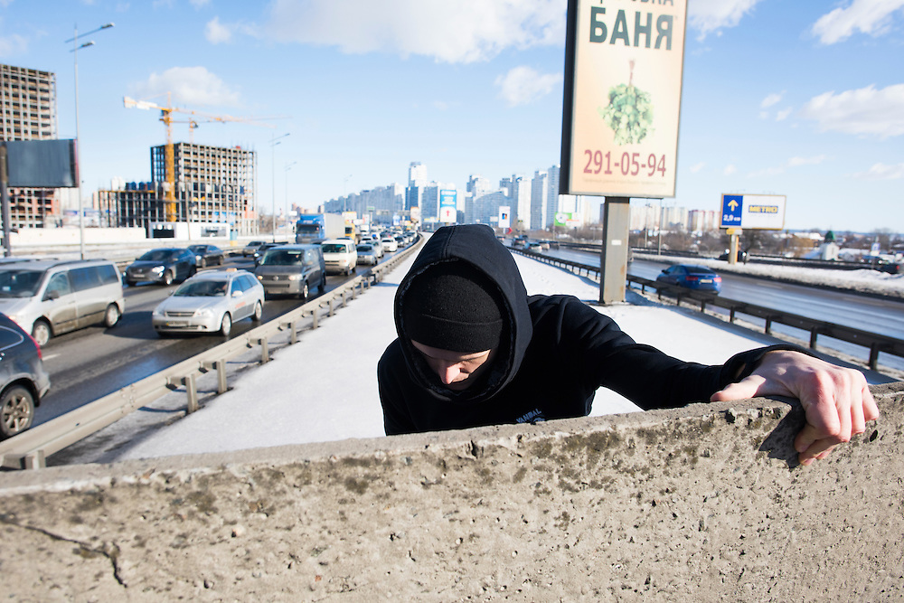 """Extreme climber Mustang Wanted climbs over a wall surrounding the approach to Pivdennyi (""""Southern"""") Bridge on February 15, 2017 in Kiev, Ukraine."""