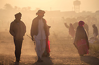 PUSHKAR, INDIA - CIRCA NOVEMBER 2016: People wailking early morning in the Pushkar Camel Fair grounds. It is one of the world's largest camel fairs. Apart from the buying and selling of livestock, it has become an important tourist attraction.