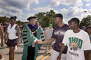 16597Freshman Convocation March from Convo to College Green: Pres. McDavis greeting walking w/students..Reuben S. Dlamini shakes hand with Dr. McDavis..other: Ahmed K. Amihene