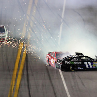 NASCAR Sprint Cup drivers Denny Hamlin (11) and Juan Pablo Montoya (42) crash on the front stretch during the NASCAR Coke Zero 400 Sprint series auto race at the Daytona International Speedway on Saturday, July 6, 2013 in Daytona Beach, Florida.  (AP Photo/Alex Menendez)