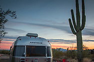 Camper trailer parked next to Saguaro cactus at a campsite in Organ Pipe Cactus National Monument, AZ, as the sunset colors appear in the sky.