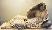 Painted terracotta sarcophagus of Seianti Hanunia Tlesnasa.  Etruscan, about 150-130 BC.  From Poggio Cantarello, near Chiusi.  The dead woman, her name inscribed on the base of her chest, was clearly a well-to-do-lady.  She reclines upon a mattress and pillow, holding an open-lidded mirror in her left hand and raising her right hand to adjust her mantle.
