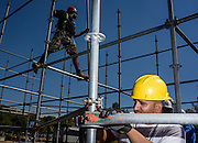 Philadelphia, Pennsylvania - September 17, 2015: Stage hands Ronnie DePamphilis, Jr, from South Philadelphia, foreground, and Danny Stowe, standing on the scaffolding help build the media riser for Pope Francis's visit to Philadelphia.<br /> <br /> <br /> Scott Mirkin's company ESM is heading the production of The World Meeting Of Families and Pope Francis's visit to Philadelphia this Fall. The events will take place along the Benjamin Franklin Parkway.<br /> <br /> CREDIT: Matt Roth for The New York Times<br /> Assignment ID: 30179397A