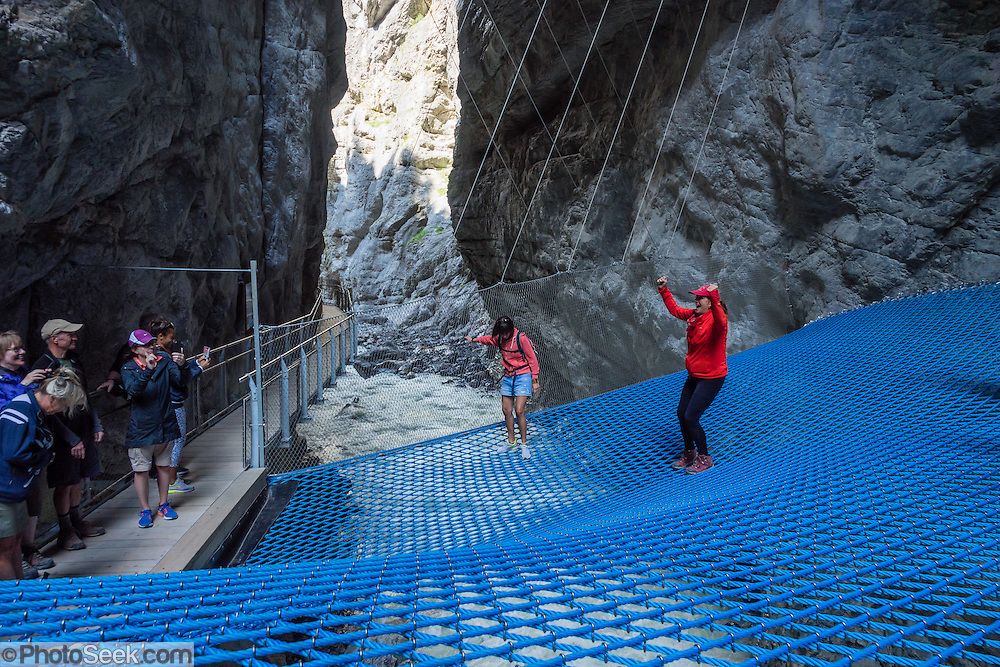 Walk across a blue net suspended over the White Lütschine river gorge, in the Gletscherschlucht of Grindelwald, Switzerland, Europe. Walk boardwalks and tunnels through the dramatic Gletscherschlucht, a deep gorge of the White Lütschine river, flowing from Lower Grindelwald Glacier. From Gletscherschlucht hotel restaurant in Grindelwald, a wooden walkway leads over raging water, through galleries and rocky tunnels over 1000 meters into the ravine, under 100-meter high cliffs. Visitors can amble on a blue net over the foaming torrent. Walk there in 35 minutes from the center of Grindelwald, or take the bus.