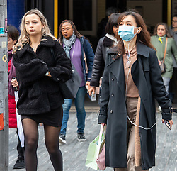 © Licensed to London News Pictures. 11/03/2020. London, UK. A young women heading to work in a mask walks down the King's Road in Chelsea as Health Minister Nadine Dorries goes in to self-isolation after catching Covid19. Yesterday British Airways cancelled all flights to and from Italy as fears over the Coronavirus disease continues. Photo credit: Alex Lentati/LNP
