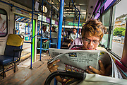 19 JUNE 2013 - YANGON, MYANMAR:  A man reads a newspaper on a bus in Yangon. The Burmese newspaper industry has enjoyed explosive growth this year after private ownership was allowed in 2013. Private newspapers were shut down under former Burmese leader Ne Win in the early 1960s. The revitalized private press is a sign of the dramatic changes sweeping Myanmar, formerly Burma, in the last three years.    PHOTO BY JACK KURTZ