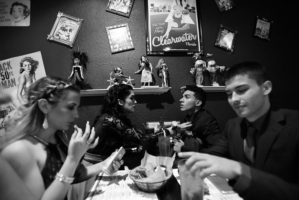 Ariel Zavala, back left, straightens Diego Lopez's tie as her friends Alexis Berrios and Sean Murray enjoy dinner at Hamburger Mary's Saturday, April 30, 2016 in Clearwater. Zavala who is transitioning from male to female attended her prom for Alonso High School on Saturday. CHRIS URSO/STAFF
