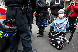 © licensed to London News Pictures. London, UK 17/03/2012. A UK Uncut protester is sitting on the road to block the police van as the UK Uncut protesters started to march after the protest outside Department of Health, London, against the Government's Health and Social Care Bill currently passing through Parliament. Photo credit: Tolga Akmen/LNP