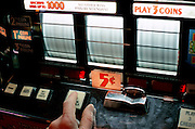 finger pushing button on slot machine